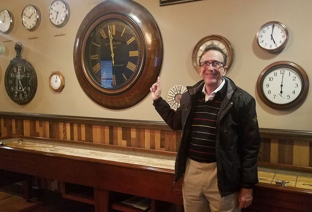 Architect Ward Bucher shows off the clocks on the walls at Clock Restoration REstaurant and Bar at QG
